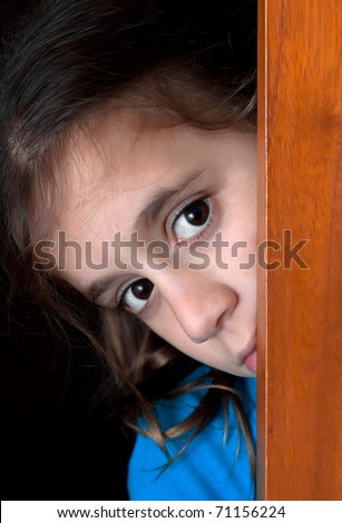 Beautiful girl hiding behind a wooden window