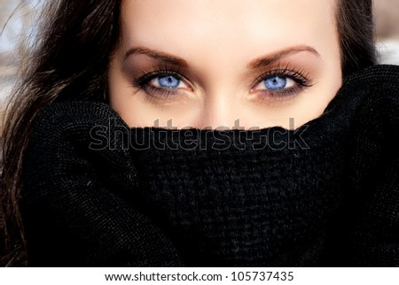 beautiful girl hiding from the wind with a black scarf