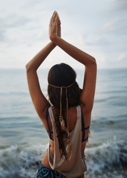 Beautiful girl hippie standing back and looking at the sea. Yoga and meeting the dawn. Tranquility and meditation.