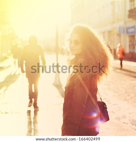 Beautiful girl hipster on the street with a camera in bright sunlight