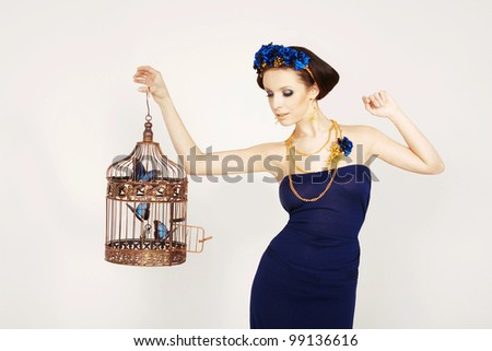 Beautiful girl holding a gold cage with blue butterflies - stock photo