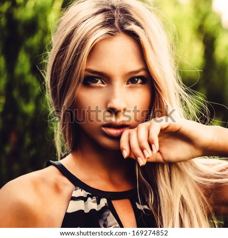 Beautiful girl holding a hand to his face, close-up portrait
