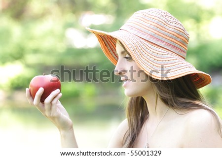Beautiful girl holding a red apple outdoors, suitable for a variety of nature, organic eating, cooking, designs