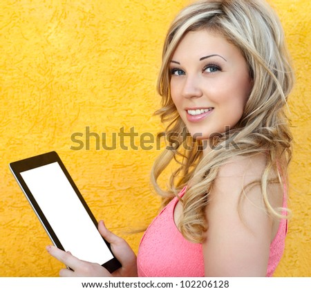 beautiful girl holding a tablet touch pad computer gadget on a yellow background