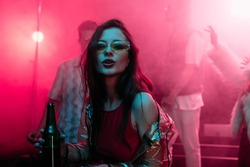 beautiful girl holding beer in nightclub and dancing during rave