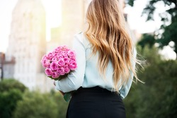 Beautiful girl holding bouquet of pink roses flowers on dating in the city. Businesswoman with bunch of flowers. View from the back.