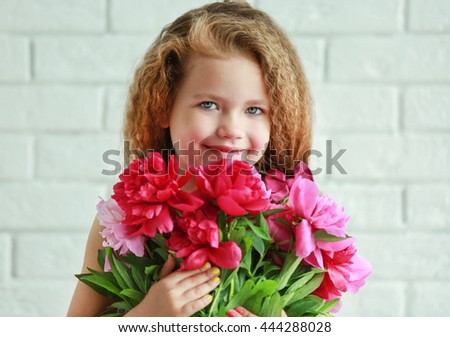 Beautiful girl holding fresh peonies bouquet on brick wall background #444288028