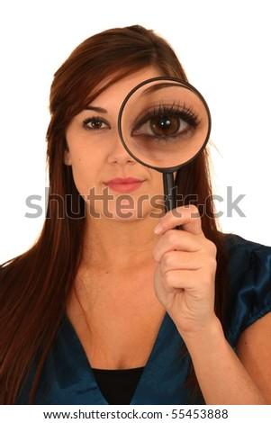 Beautiful girl holding magnifying glass showing big eye