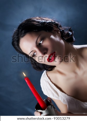 Beautiful girl holding red candle and look at the flame/Candle and Beauty