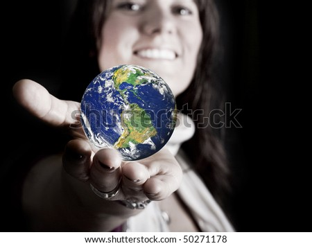 Beautiful girl holding the planet Earth in her hand. Photo montage on black background, concept of preservation, giving and sharing