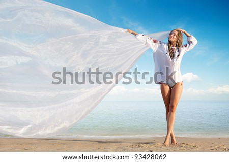 Beautiful girl holding white cloth against blue sky