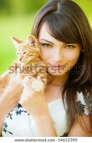 Beautiful girl holds on hands of kitten.