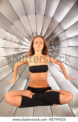 beautiful girl hovers in air with closed eyes in studio; silver umbrella in background