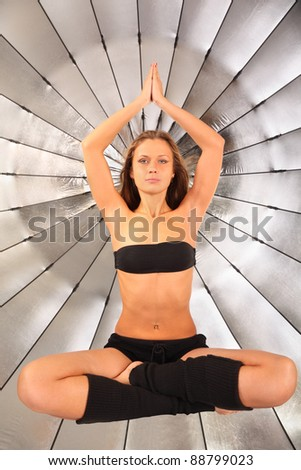 beautiful girl hovers with opened eyes in studio; silver umbrella in background