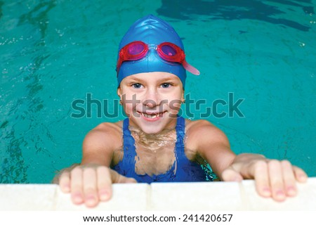 beautiful girl in a bathing suit, swim cap, goggles, holding on overboard in a swimming pool
