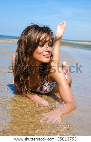 Beautiful girl in a bikini lies on the beach in the water