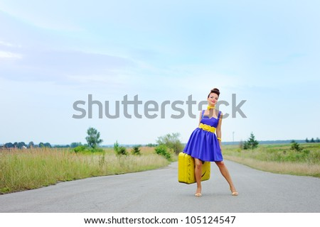 beautiful girl in a blue dress with a yellow suitcase on the road