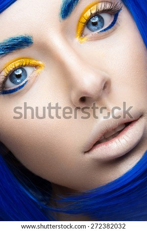 Beautiful girl in a bright blue wig in the style of cosplay and creative makeup. Beauty face. Art image. Picture taken in the studio on a yellow background.