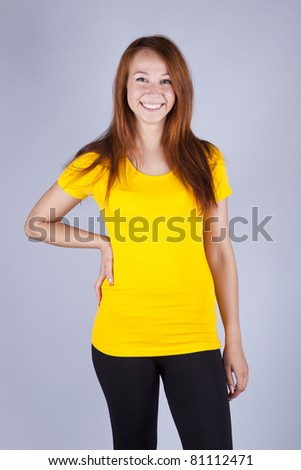 beautiful girl in a bright yellow T-shirt stands on a gray background