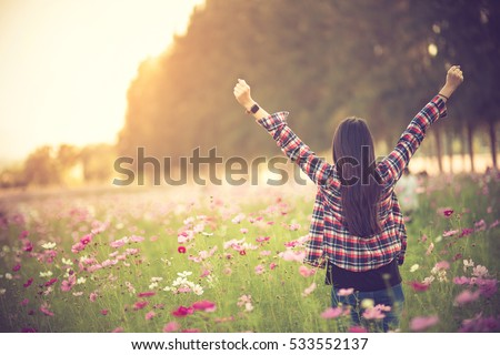 beautiful girl in a cosmos flower field at sunset. concept of freedom.Vintage color