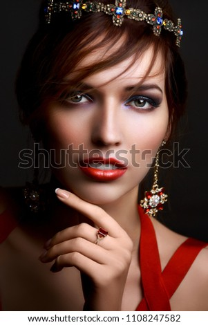 Beautiful girl in a crown and earrings on a dark background. Red dress and  red aa44559a9c38