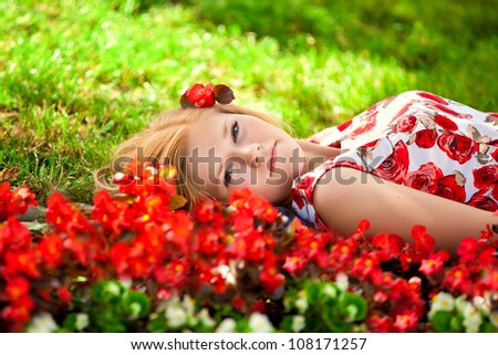 beautiful girl in a dress lies among a grass and red flowers