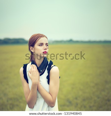 beautiful girl in a field. vintage photo