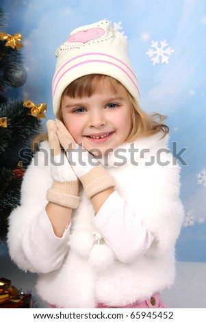 beautiful girl in a fur cape, hat and gloves around the Christmas Tree