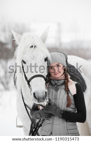 Beautiful girl in a gray vest hugs muzzle of horse breeds Arab