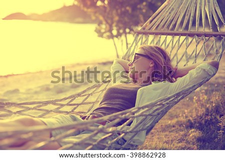 beautiful girl in a hammock on the beach, watching the sunset. Image with retro filter