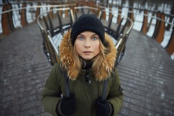 beautiful girl in a hat and winter jacket on the background of the bridge. looking at the camera