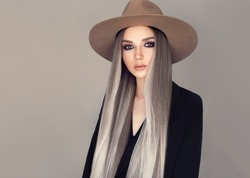 Beautiful girl in a hat with long blonde straight hair . Fashionable coloring of shatush. Beauty, cosmetics and fashion