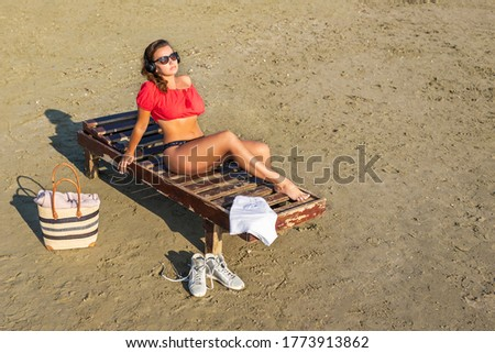Beautiful girl in a headphones in a shorts and blouse is relaxing on wooden lounge chair on a sandy beach by the sea. Top view. Sunset.