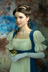Beautiful girl in a historical dress in the Empire style of the early 19th century on an unusual blue background with streaks and flowers