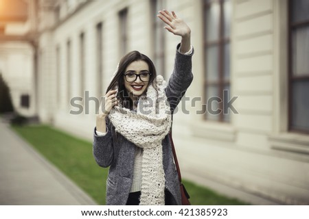 97ff1ac9cd Beautiful girl in a knitted scarf and sunglasses waving to someone   421385923