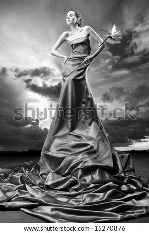 Beautiful girl in a long dress holds exotic flower in a hand. Against backdrop of cloudy skies
