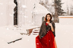 Beautiful girl in a long red dress and a scarf on his shoulders walking down the street in winter. Girl wrapped in a warm shawl in winter outside in a Blizzard