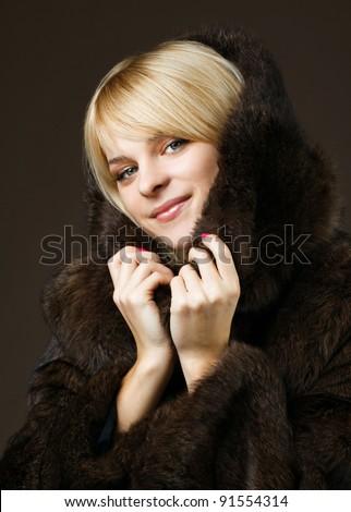 Beautiful girl in a natural fur coat fur