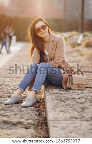 Beautiful girl in a park. Stylish brunette in a brown jacket. Lady in a sunglasses #1363755077