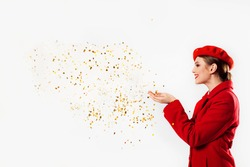 beautiful girl in a red coat and a red beret blowing magic stars. holiday, flying sparkles and tinsel. Birthday party for valentines day or christmas.