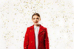 beautiful girl in a red coat and a red beret blowing magic stars. holiday, flying sparkles and tinsel. Joyful and absent-minded. surprise to the unusual.Birthday party for valentines day or christmas.