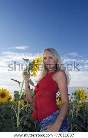 Beautiful girl in a red dress and jeans holds in a hand a sunflower in a field. Summer evening. Blue sky and white clouds above sunflower field