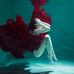 beautiful girl in a red dress swims under water. amazing Underwater beauty photo. Dive under the water, surrealism, and concept