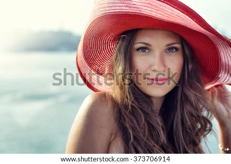 Beautiful girl in a red hat smiling at the summer waterfront #373706914