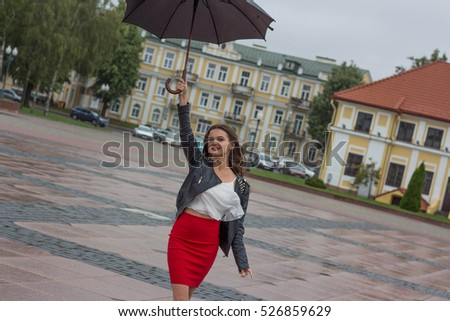 393d31a97f6d Beautiful girl in a red skirt and a blouse with an umbrella on a cloudy  summer