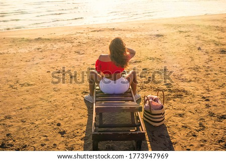Beautiful girl in a shorts and blouse is relaxing on wooden lounge chair on a sandy beach by the sea. Top view. Sunset.