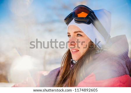 beautiful girl in a ski jacket and glasses spring on a Sunny spring day in the mountains #1174892605