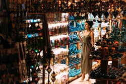 Beautiful girl in a souvenir shop in Turkey. Girl chooses a souvenir Oriental shop. Street shop. Turkish Souvenirs. Oriental bazaar. Turkish Bazaar. Tourist shop. Moroccan Bazaar. Copy space