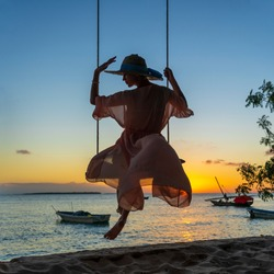 Beautiful girl in a straw hat and pareo swinging on a swing on the beach during sunset of Zanzibar island, Tanzania, east Africa. Travel and vacation concept