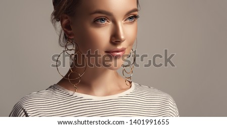 Beautiful girl in a striped T-shirt. Fashionable and stylish women's clothing . Fashion look  , beauty and style. Young woman in trendy jewelry earrings rings.